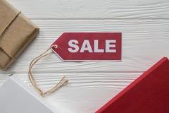 Remise sur des articles sur le fond en bois blanc avec le tad rouge Images stock