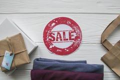 Remise sur des articles sur le fond en bois blanc dans le style de denim avec le label rouge Photos libres de droits