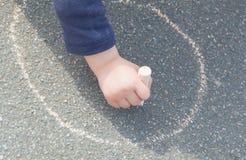Remisy na asfalt kredzie z dziecko ręką Fotografia Stock