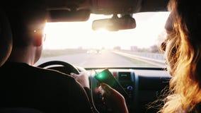 Remita a lo largo de la carretera hacia el sol Un par joven está viajando en un coche en los rayos del sol poniente back almacen de metraje de vídeo