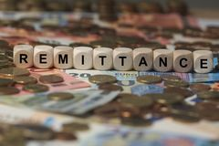 Remittance - cube with letters, money sector terms - sign with wooden cubes Stock Images