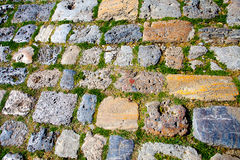 Remnant of ancient pavement. With large stones and grass growing in between Stock Photo