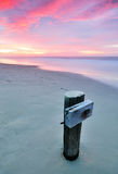 Remnant of Jetty at the Beach with colorful sky Stock Photo