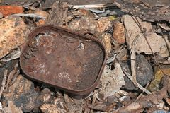 REMNANT OF OLD RUSTED SARDINE TIN. View of old rusted sardine can lying between rocks and rubble Royalty Free Stock Photo