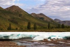 Remnants of spring ice in the valley of a mountain river. Royalty Free Stock Photos