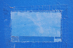 Remnants of tape and sign on overpainted blue wall Stock Images