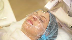 Remoção ascendente próxima do laser do procedimento de pontos pretos da pele de uma jovem mulher em uma clínica cosmética vídeos de arquivo
