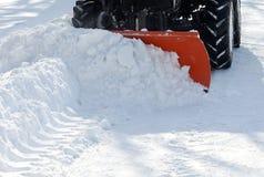 Remoção de neve pequena do trator no parque imagem de stock