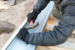 Remodel renovation house concept. Photo of professional workman with hand tool work on incomplete roof, make laying rafters on. Small wooden building royalty free stock photo