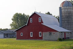 A Remodeled Barn and Silo. The red barn has been remodeled and a new roof has been installed. The silo has a rusted roof and is made of cement blocks Stock Photos