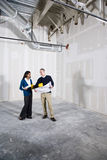 Remodeling new unfinished office space. Multi-ethnic people in office space ready for renovations by new tenant Stock Photo