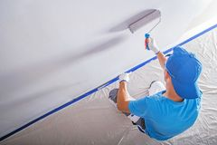 Remodeling and Painting. Apartment Remodeling and Painting by Caucasian Construction Worker stock images