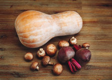 Remolachas púrpuras, calabaza, setas frescas en la tabla de madera El fondo vegetal de Autumn Garden Imagen de archivo