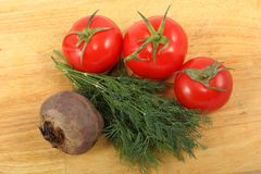 Remolachas, tres tomates maduros y manojo de las hojas frescas del eneldo en una tabla de cortar Imagen de archivo
