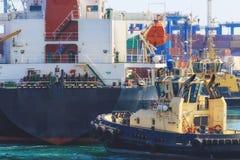 Remolcador del primer que ayuda al buque de carga maniobrado en el puerto de Odessa, Ucrania fotografía de archivo libre de regalías