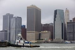 Remolcador en el río con Manhattan NYC en el fondo Foto de archivo
