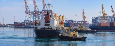 Remolcador que ayuda al buque de carga maniobrado en el puerto de Odessa, Ucrania fotos de archivo libres de regalías