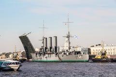 Remolque de una aurora histotical del crucero a un lugar de la reparación en el muelle, St Petersburg, Rusia Foto de archivo