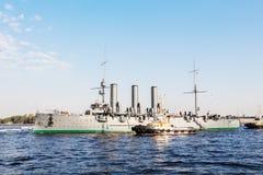 Remolque de una aurora histotical del crucero a un lugar de la reparación en el muelle, St Petersburg, Rusia Fotografía de archivo libre de regalías