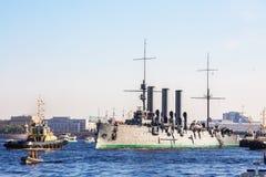 Remolque de una aurora histotical del crucero a un lugar de la reparación en el muelle, St Petersburg, Rusia Fotografía de archivo