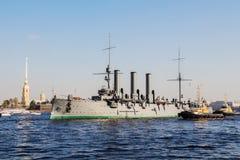 Remolque de una aurora histotical del crucero a un lugar de la reparación en el muelle, St Petersburg, Rusia Imagen de archivo libre de regalías