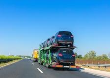 Remolque del portador de coche con los coches en la plataforma de la litera Camión del transporte del coche en la carretera Espac imagen de archivo libre de regalías