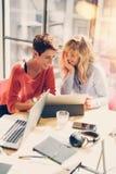 Remolque a las empresarias hermosas que hacen la conversación en la oficina moderna del estudio Compañeros de trabajo hermosos en Imagen de archivo