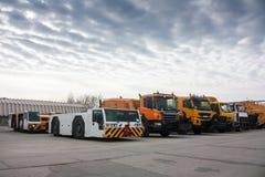 Remolque los tractores y los camiones de la limpieza en el aeropuerto Fotografía de archivo