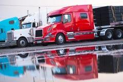 Remolque moderno de la cama plana del camión del aparejo grande semi con el cargo en el estacionamiento Imágenes de archivo libres de regalías