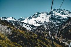 Remonte de Almaty, Kazajistán, cabina del teleférico en Medeo a la ruta de Shymbulak contra fondo de la montaña Imagen de archivo libre de regalías