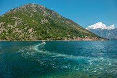 Remonte en el agua en una motora, en el fondo una pequeña ciudad Perast, bahía de Kotor Boka Kotorska, Montenegro Visión desde foto de archivo libre de regalías