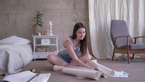 Remontowy mieszkanie, młoda kobieta w drelichowych kombinezonach ciie nową tapetową rolkę z nożycami wtedy przegląda z uśm zbiory
