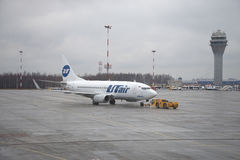 Remorquage d'aviation de Boeing 737-500 (VQ-BJQ) UTair d'avions sur l'aérodrome Aéroport de Pulkovo, St Petersburg Photo stock