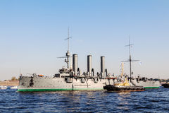 Remorquage d'une aurore de croiseur à un endroit de la réparation dans le dock, St Petersburg, Russie Photographie stock libre de droits