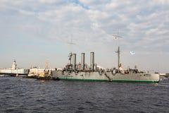 Remorquage d'une aurore histotical de croiseur à un endroit de la réparation dans le dock, St Petersburg, Russie Photographie stock libre de droits