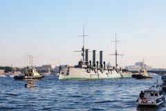 Remorquage d'une aurore histotical de croiseur à un endroit de la réparation dans le dock, St Petersburg, Russie Photo stock