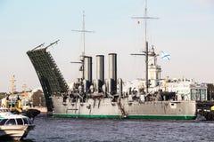 Remorquage d'une aurore histotical de croiseur à un endroit de la réparation dans le dock, St Petersburg, Russie Photographie stock