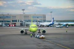 Remorquage du plan VP-BTV d'Airbus A319 de la ligne aérienne S7 le soir de mai à l'aéroport de Domodedovo Images libres de droits