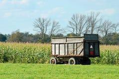 Remorque de ferme par une zone de maïs Photo stock