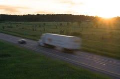 Remorque de tracteur dans le mouvement au coucher du soleil Images stock