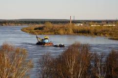 Remorqueur transportant une grue de rivière le long du lit de rivière Photo libre de droits