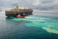 Remorqueurs aidant le navire porte-conteneurs image stock