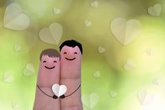 Remorquez le doigt tenant le coeur et le visage de sourire avec amour de bokeh Images stock