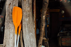 Remos anaranjados en un fondo de madera Dos paletas anaranjadas para un barco de mar o un kajak imagen de archivo