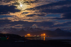 Remote Alaskan fishing village, snowy mountains and colorful clouds illuminated by a full moon at night Stock Images