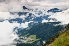 Remote alpine village and dark green forest Carnic Alps Italy stock images