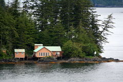 Remote Cabin. A single cabin on a remote island among tall pine trees Stock Photo