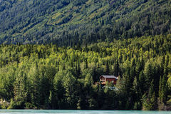 Remote cabin in Alaskan mountain wilderness on remote lake Royalty Free Stock Photography