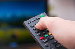 Remote control. Black remote control changing channel on TV Royalty Free Stock Image