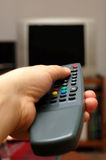 Remote control. Hand using a remote control. TV blurred in the background Royalty Free Stock Photos